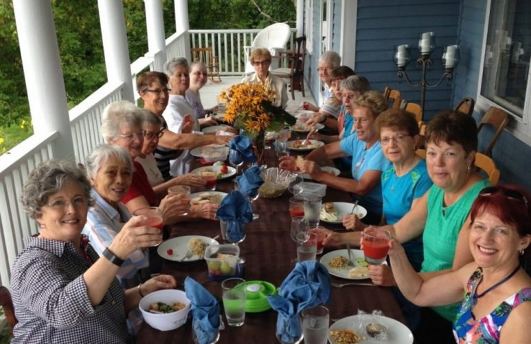 Family and friends meal on the front porch of the Lumber Baron's House / Repas de groupe sur le balcon avant de la Maison des barons forestiers